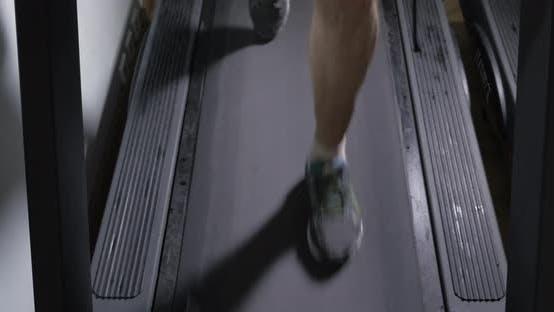 Adult male in sneakers walking on a treadmill