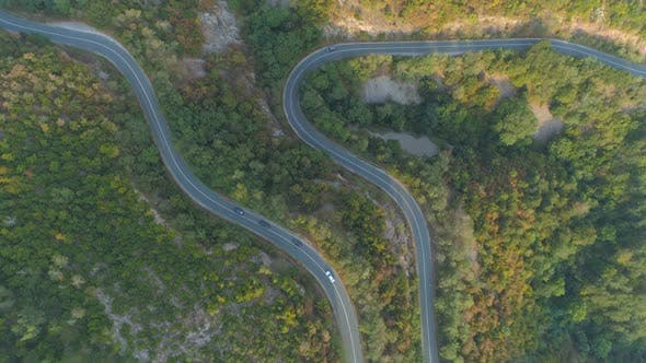 Thumbnail for Drone Following Three Cars Driving in Front of a White Truck Along Curvy Mountain Forest Road
