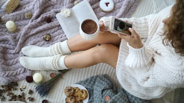 Thumbnail for Blogger Taking Pictures With Smartphone Of Legs In Knit Socks And Hot Chocolate