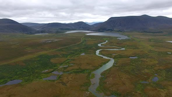 Thumbnail for Flying Over River In Tundra To Mountains