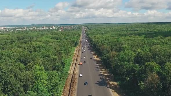 Thumbnail for Long Straight Highway Through Dense Forest, Aerial Shot in Summer Day, Picturesque Clouds on Horizon