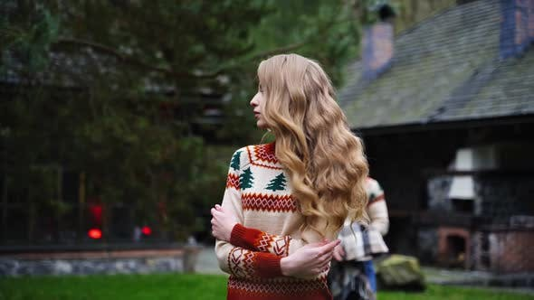 Young handsome man covers beautiful girl with blanket outside. Same sweters