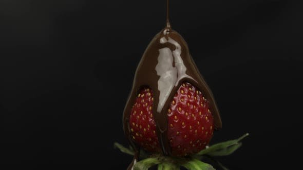 Thumbnail for Ripe Juicy Strawberry Are Poured Over Chocolate on a Black Background. Close Up