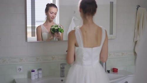 Romantic Happy Slim Young Bride Reflecting in Mirror in Bathroom Smelling Bouquet Smiling