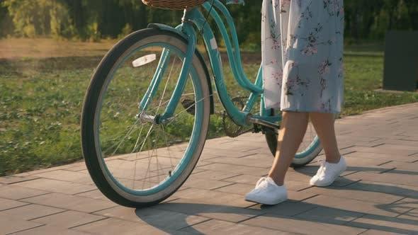 Thumbnail for Frau im stilvollen Outfit geht mit Vintage-Retro-Bike im Park in der Sonne