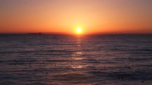 Thumbnail for Sunrise Over the Sea  We See a Cargo Ship On the Horizon