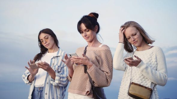 Thumbnail for Three ladies texting in their smart phones in the street.