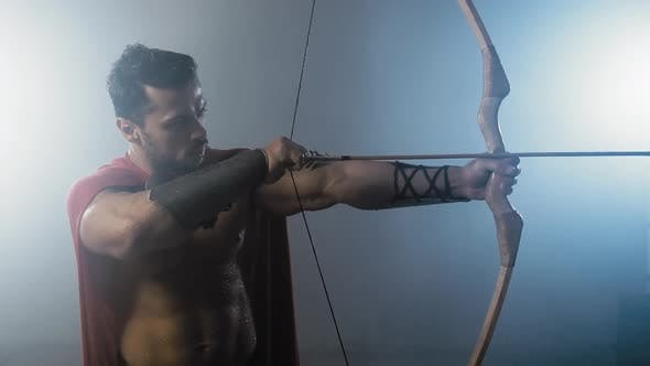 Shirtless Spartan Aiming with Arrow.