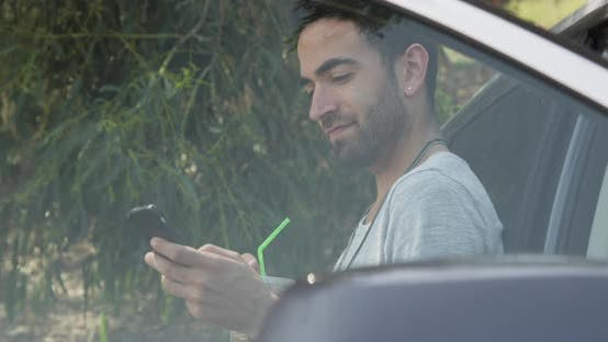 Thumbnail for Man using smartphone while waiting for roadside assistance