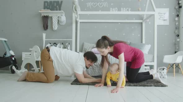 Thumbnail for Joyful Parents Crawling Together with Baby Indoors