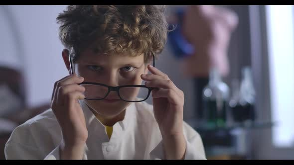 Thumbnail for Close-up of Cute Caucasian Boy with Curly Hair Taking Off and Putting on Eyeglasses. Clever Teenager