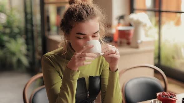 Junge Frau schnüffelt ein Aroma von Tee in einem Café