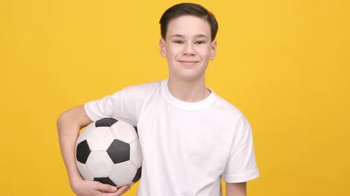 Teenager Boy Posing Holding Soccer Ball Standing Over Yellow Background
