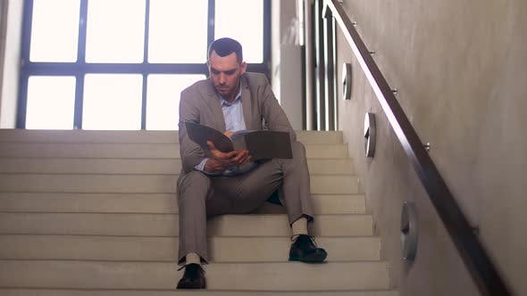 Thumbnail for Businessman with Folder Sitting on Stairs 32