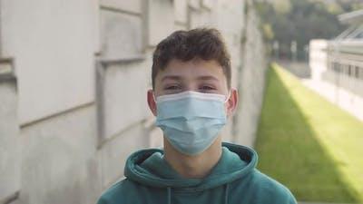 Joyful smiling student in a medical mask