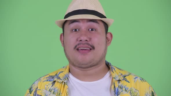 Thumbnail for Face of Happy Young Overweight Asian Tourist Man Nodding Head Yes