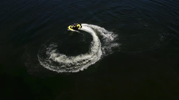 Thumbnail for Aerial drone shot of man riding personal water craft on lake
