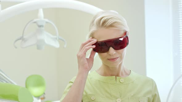 Thumbnail for Beautiful Female Dentist Dressing Up Ultraviolet Orange Safety Goggles
