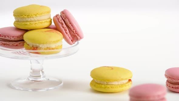 Thumbnail for Gelbe und rosa Macarons auf Glasständer und Tisch