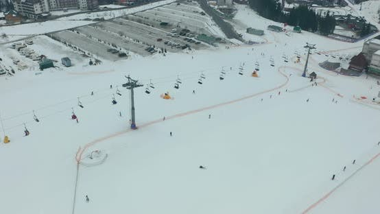 Thumbnail for Aerial View: Ski Resort, Slope and Chair Lift. Cableway Lifts Skiers To the Mountain Hill. Winter