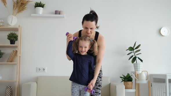 Mother with Daughter Exercising with Dumbbells