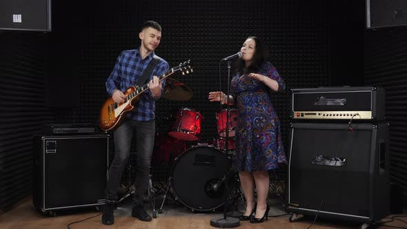 Two musicians are rehearsing at vocal recording studio, singing songs, dancing and having fun