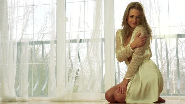 Thumbnail for A Young Beautiful Woman in White Nightwear Kneels on a Wooden Floor, Poses and Smiles at the Camera