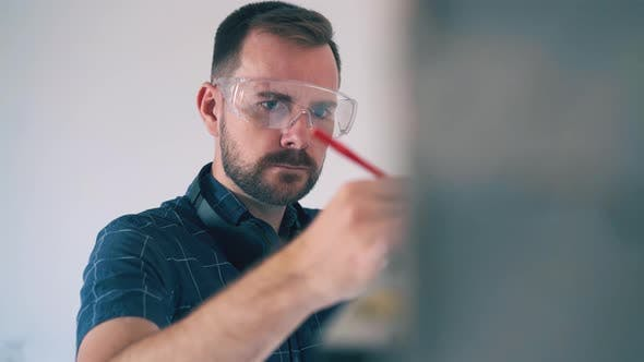 Builder in Goggles Tired of Checking Wall Angle in Room
