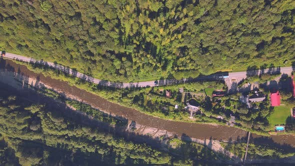 Aerial View on Top Flight Over the River and the Road with Cars Among the Dense Green Forest. The