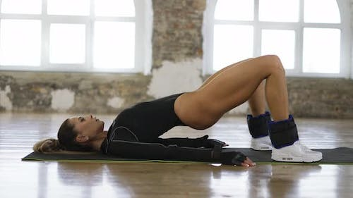 Sexy Woman Making Buttocks Exercise on Mat in Bright Studio
