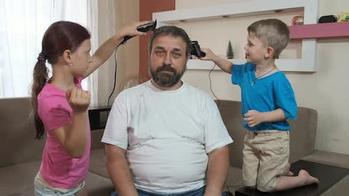 A young son and daughter cut their father's hair on his head with an electric clipper