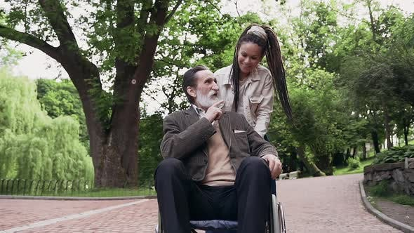 Thumbnail for Trendy Grandaughter and Her Bearded Sedentary Bearded Granddad in Wheelchair Having Fun Together