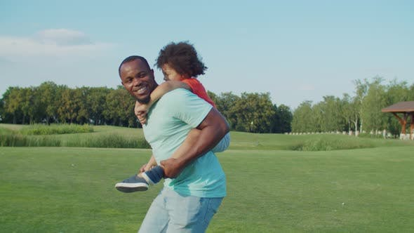 Thumbnail for Joyful Dad Piggybacking Excited Son in Nature