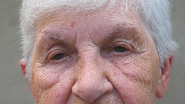 Thumbnail for Close Up Gray Eyes of Grandmother with Wrinkles Around Them. Portrait of Senior Lady Looking Into