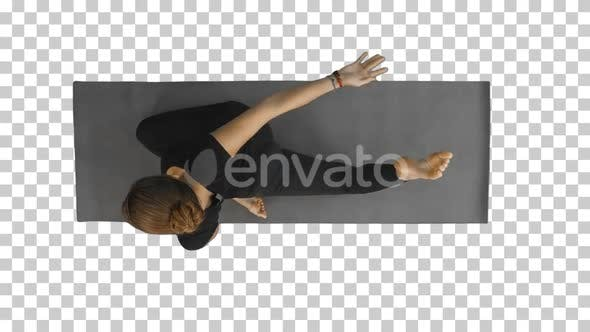 Woman holding a downward facing dog pose on a mat, Alpha Channel