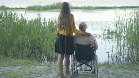 Thumbnail for Back View of Caucasian Couple Admiring Sunset on River Bank. Young Woman and Disabled Man on
