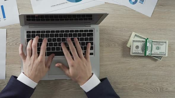 Thumbnail for Man Typing on Laptop, Dollar Bills in Straps Appearing, Earnings, Time Lapse