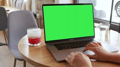 The unrecognizable person working on Macbook Pro 16 laptop notebook green screen chromakey monitor.