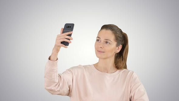 Thumbnail for Smiling young woman taking a selfie smiling on gradient background.