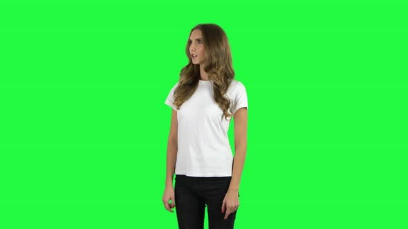 Cover Image for Lovable Girl Listens Attentively and Nods His Head Pointing Finger at Viewer. Green Screen