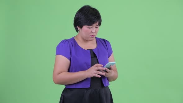 Thumbnail for Happy Young Overweight Asian Woman Using Phone and Calling for Taxi