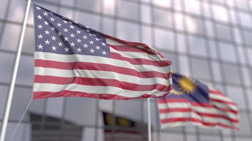 Flags of the United States and Malaysia in Front of a Skyscraper
