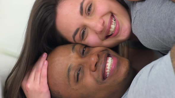 Portrait of African American and Caucasian couple lying down