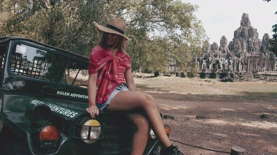 Female Model Lying on Top Of a Vehicle at the Background of Marvelous Ruins