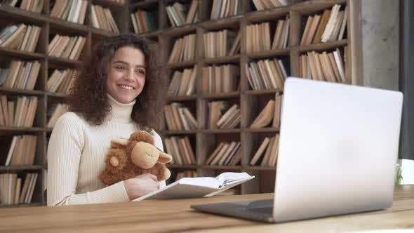Smiling Hispanic Teacher Reading Book During Virtual Online Kindergarten Class
