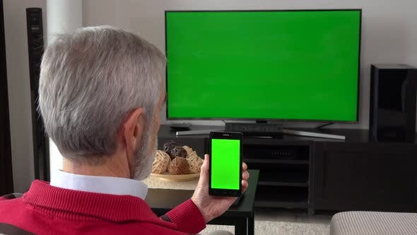 Thumbnail for An Elderly Man Watches TV with a Green Screen and Looks at a Smartphone with a Green Screen