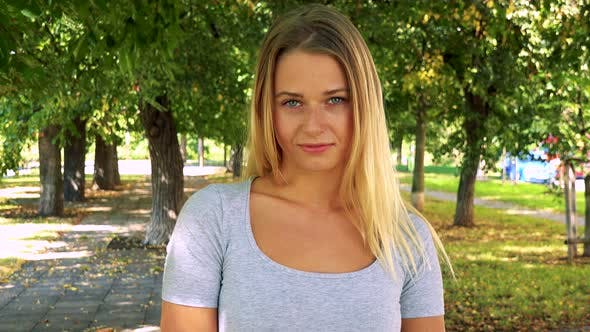 Thumbnail for Young Pretty Blond Woman Looks To Camera with Serious Face - Park with Trees in Background