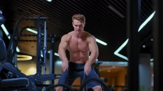 Professioneller männlicher Athlet verdreht die Seile mit seinen Händen, schüttelt die Muskeln der Hände.  Training