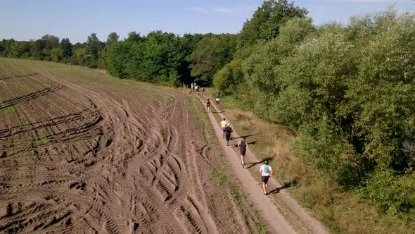 Aerial Shot of People in Trail Running Marathon in a Countryside Field Road, Slow Motion  60 Fps