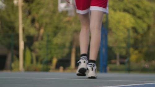 Der Basketballball liegt auf dem Sportplatz. Unerkennbarer Spieler nimmt den Ball auf und dribbeln
